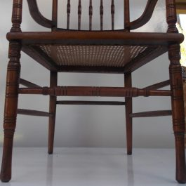 Antique Wooden Armchair With Cane Seat And Rustic Carved Design